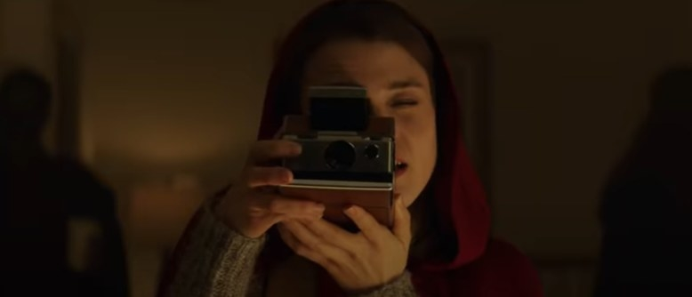 A girl taking a picture with a polaroid camera