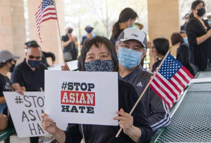 People holding #Stop Asian Hate posters and American flags