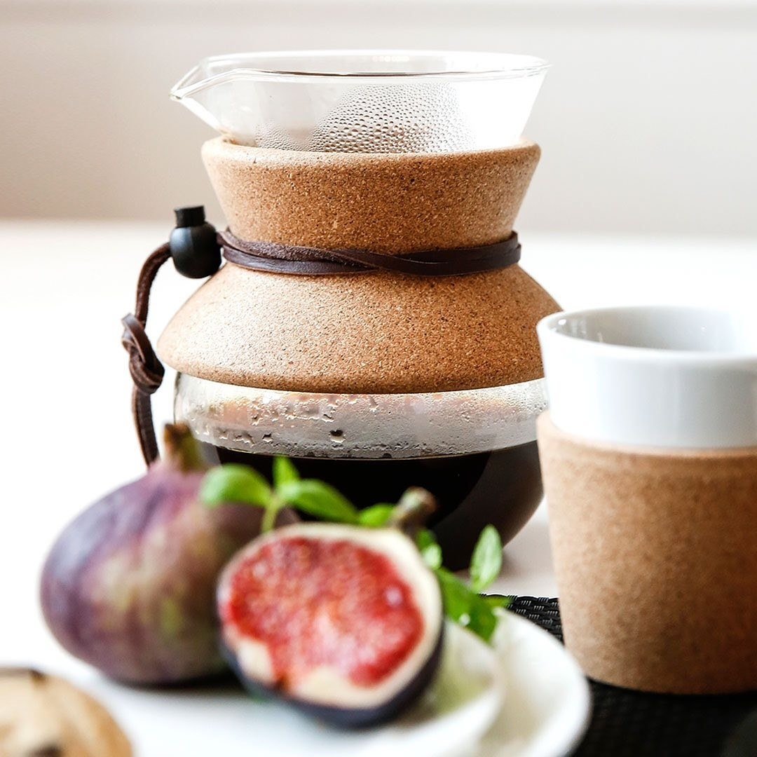 The coffee maker in front of a plate of figs