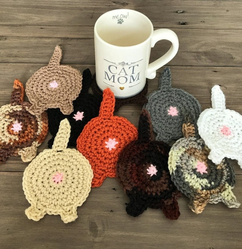 Several cat booty coasters in front of a mug