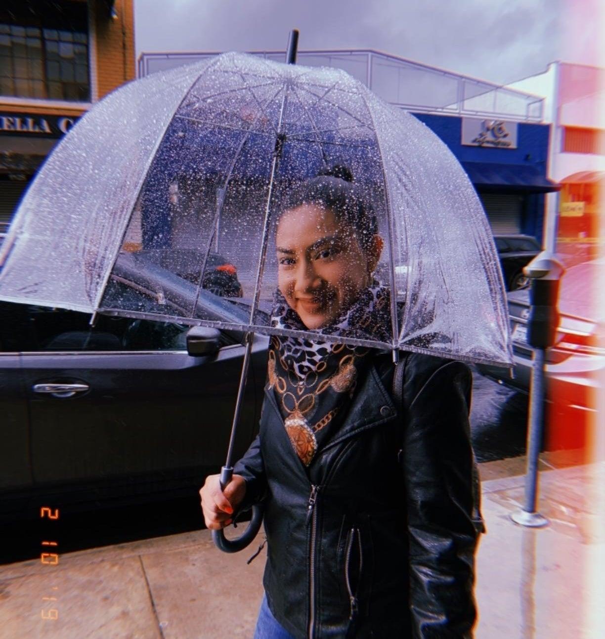 reviewer smiling through their clear umbrella