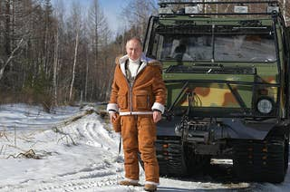 Russia's President Vladimir Putin is seen by an all-terrain vehicle in a forest  dressed in a sweatsuit