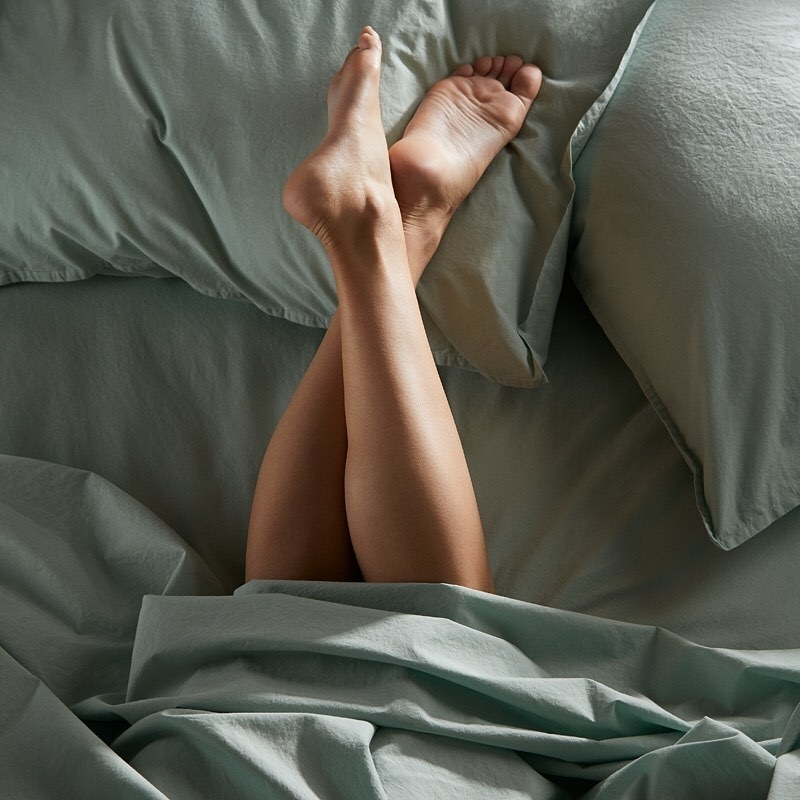 A persons tucked into the covers with their feet on the pillows