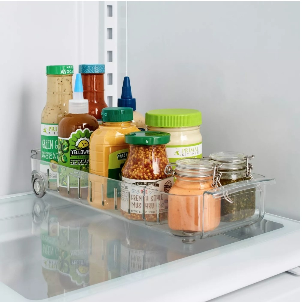 A roll out fridge caddy filled with various condiments