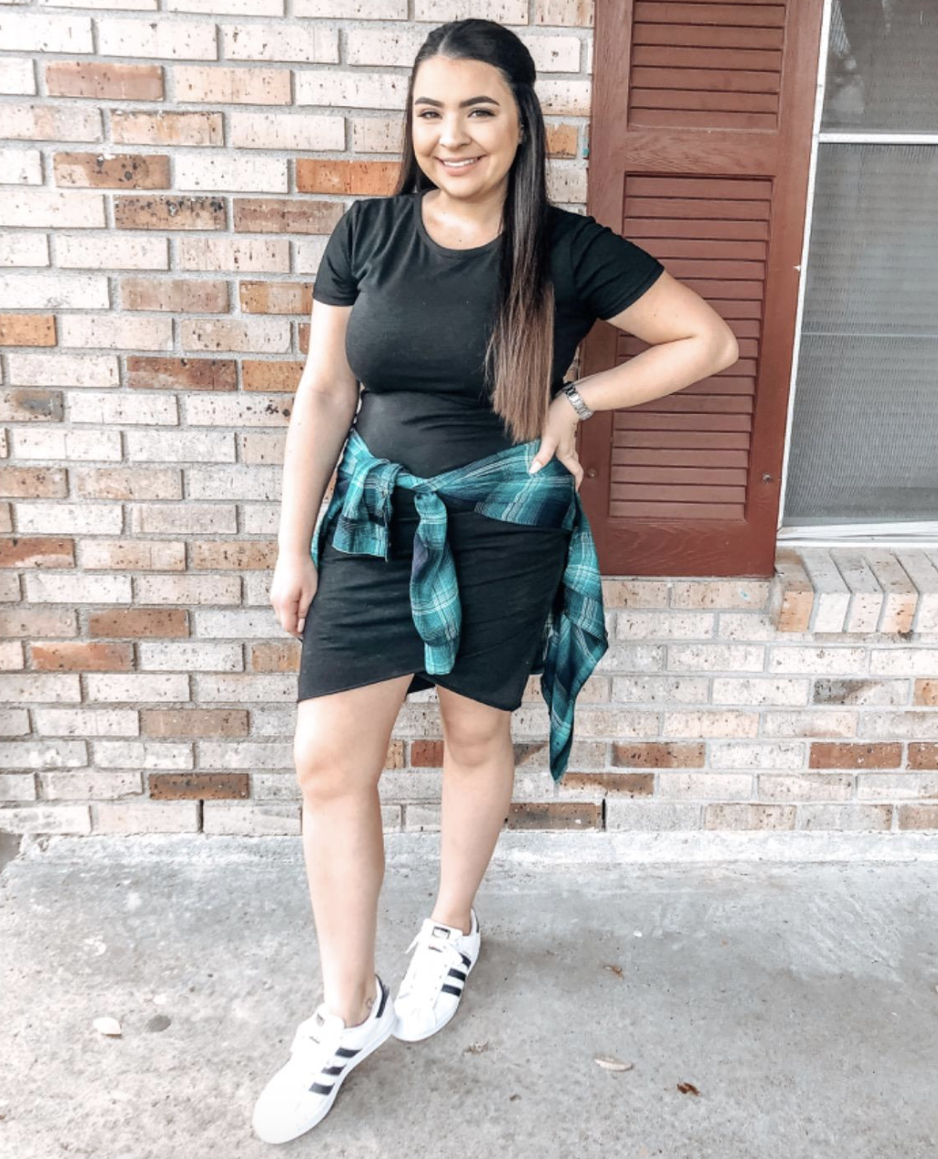 reviewer wearing the black dress with sneakers