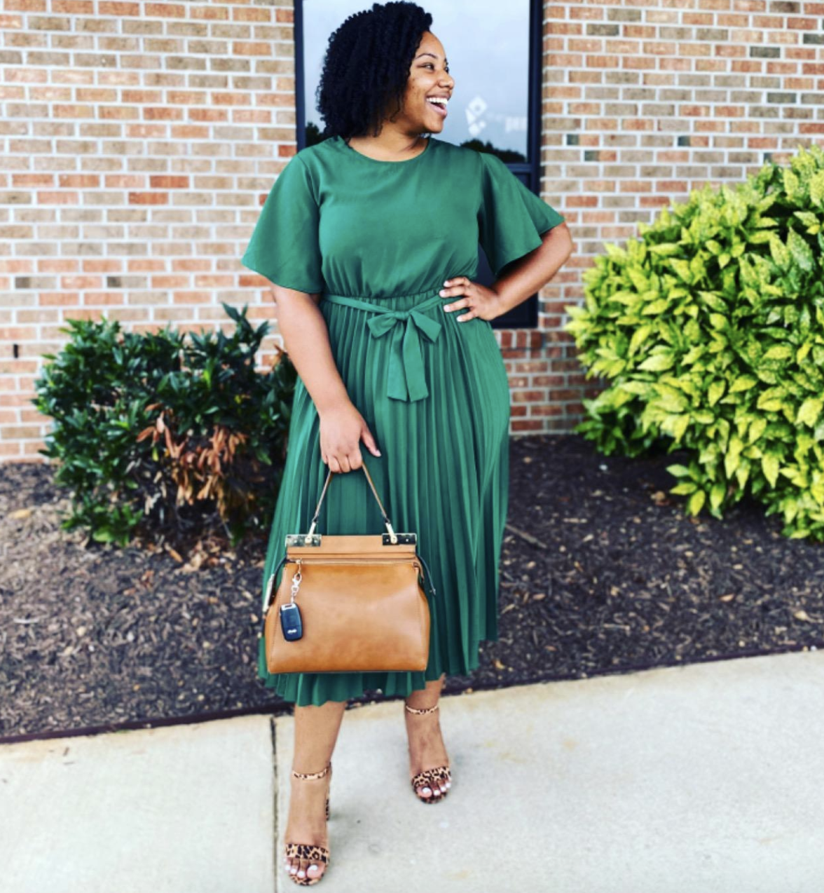 reviewer wearing the green belted dress