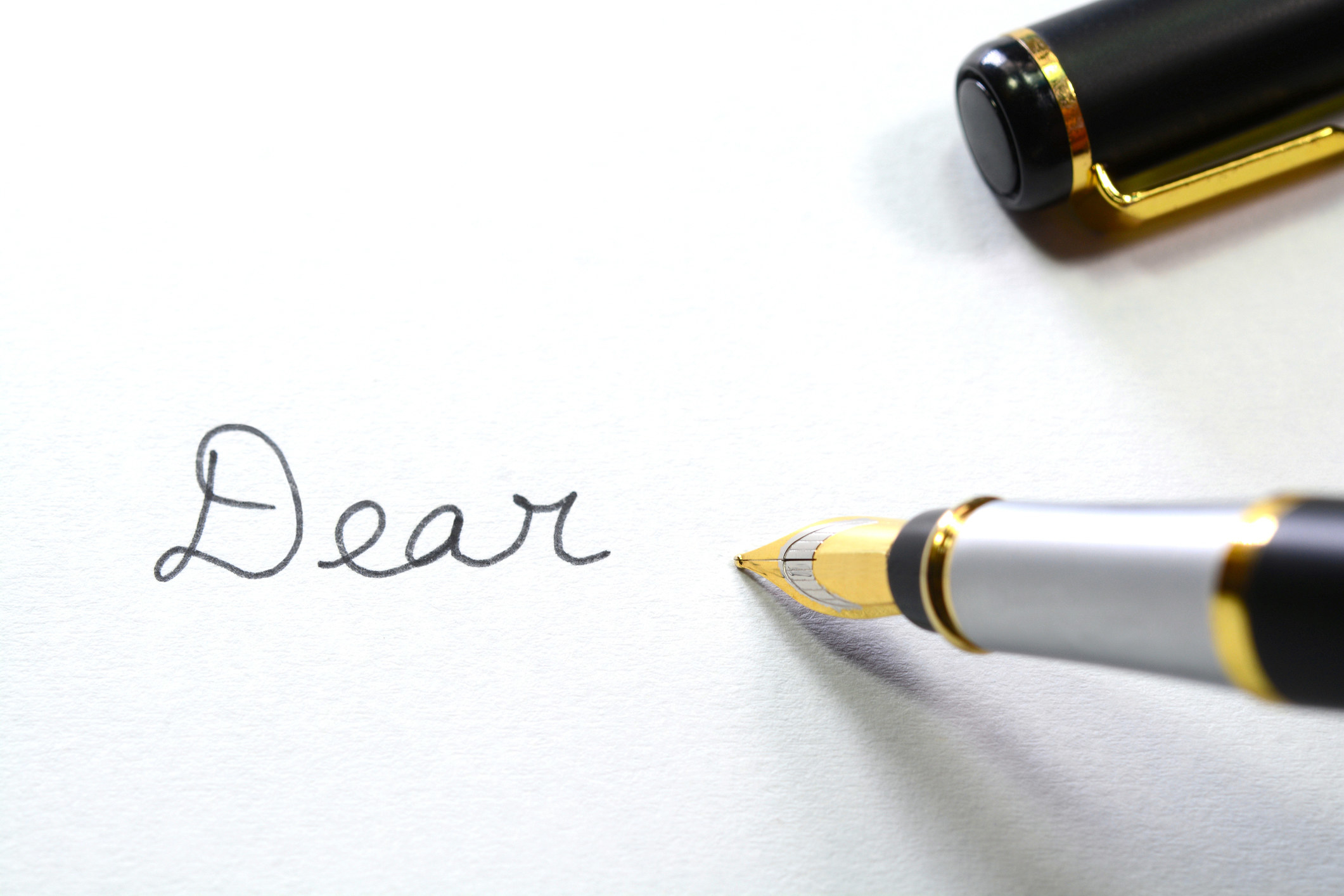 """Dear,"" written with a fountain pen in cursive"
