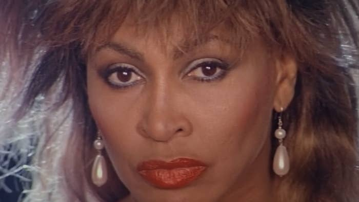 Tina Turner circa early-'80s staring into the camera, wearing makeup and pearl earrings