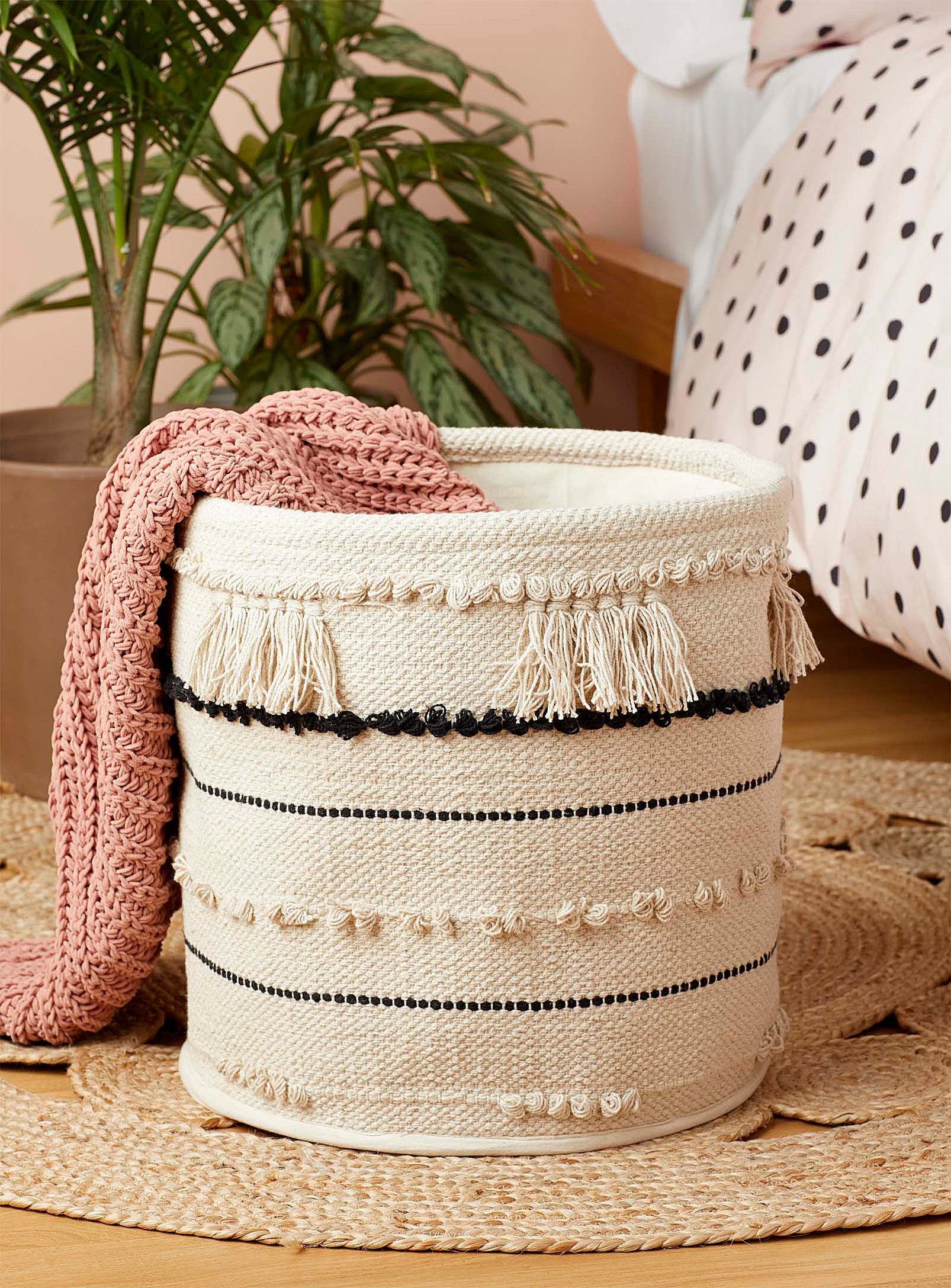 A woven basket with a blanket hanging off the edge