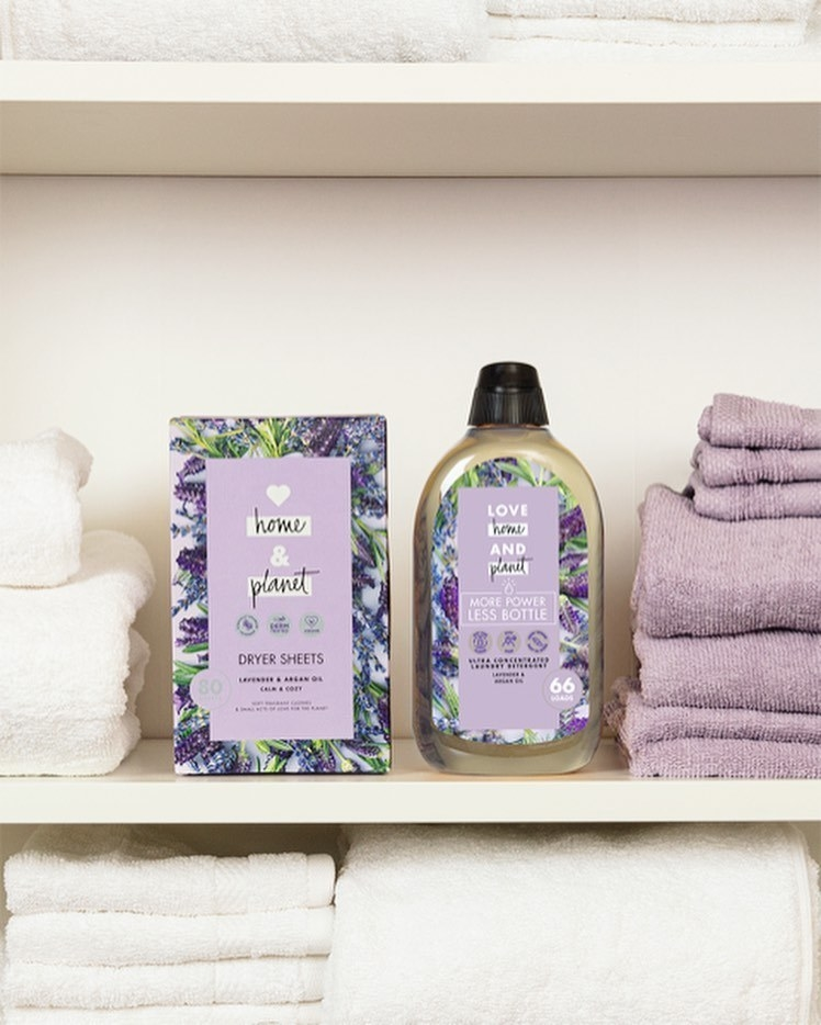 a bottle of concentrated laundry detergent in lavender packaging on a shelf next to dryer sheets and towels