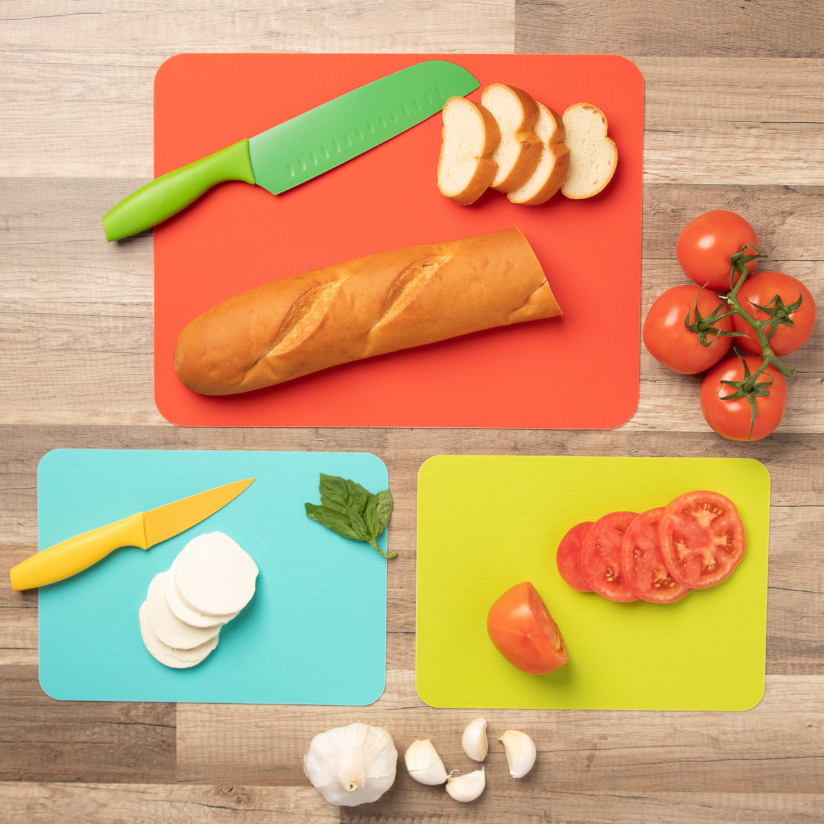 a large orange and small teal and green cutting boards on a counter with bread, tomatoes, garlic, and cheese