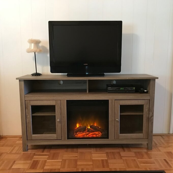 brown stand with fireplace lit