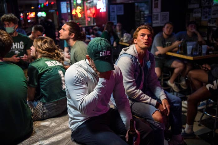 Maskless people crowd together at a bar to watch a football game