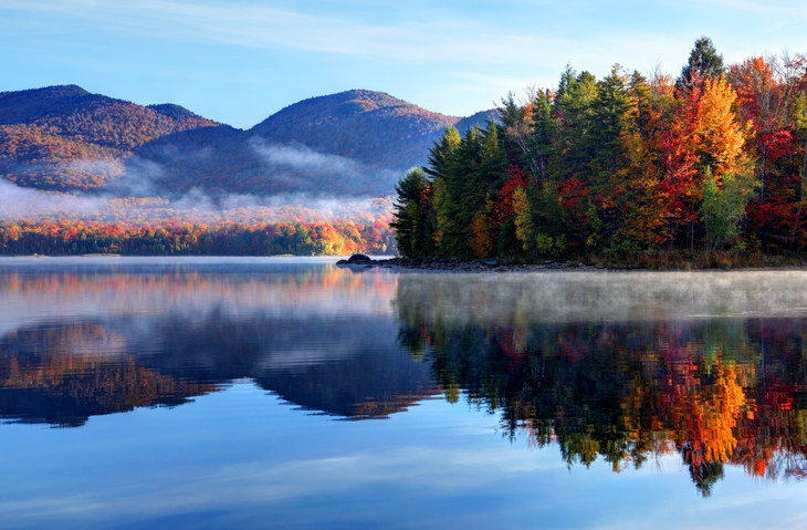 A misty lake in Vermont amid a forest full of trees during autumn