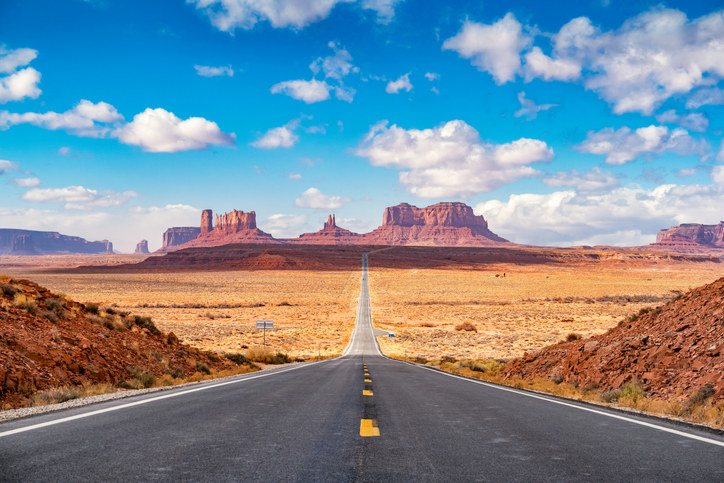 A view from the road in the middle of the Utah desert with picturesque mesas in the distance