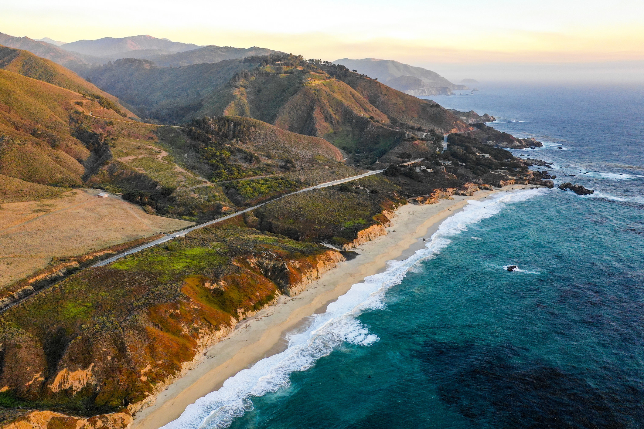 An aerial view of the coast near Big Sur with mountains and cliffs leading to a sandy beach
