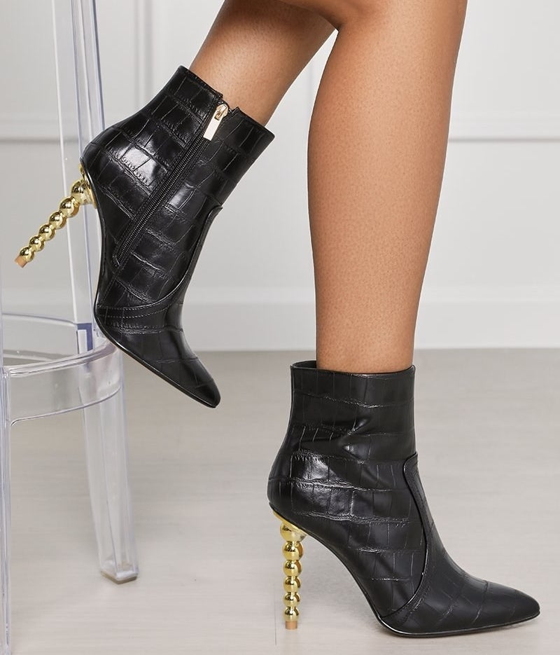 Model wearing the black croc booties with a gold pedestal heel