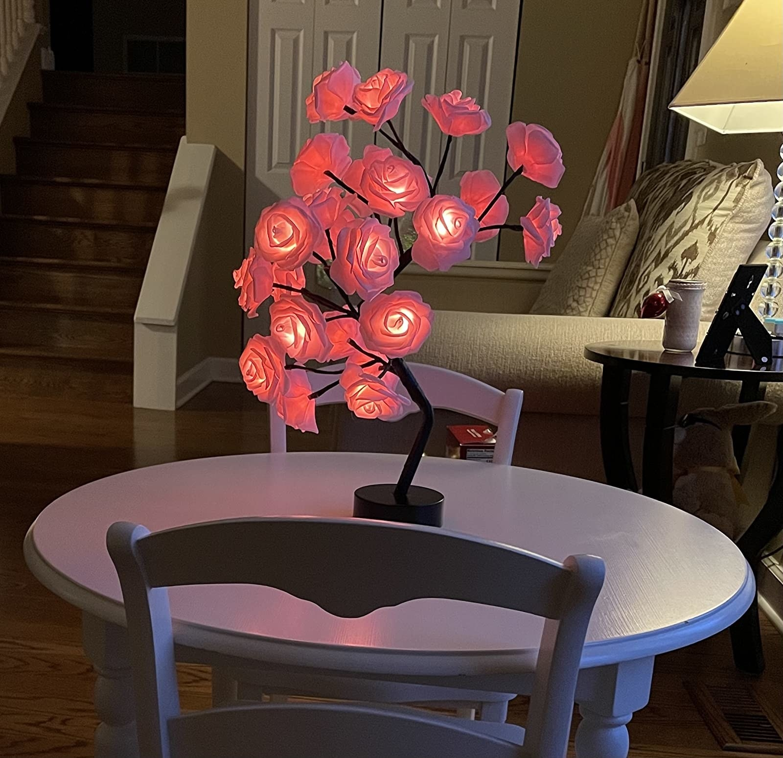 reviewer image of the rose tree lamp turned on atop a round white table