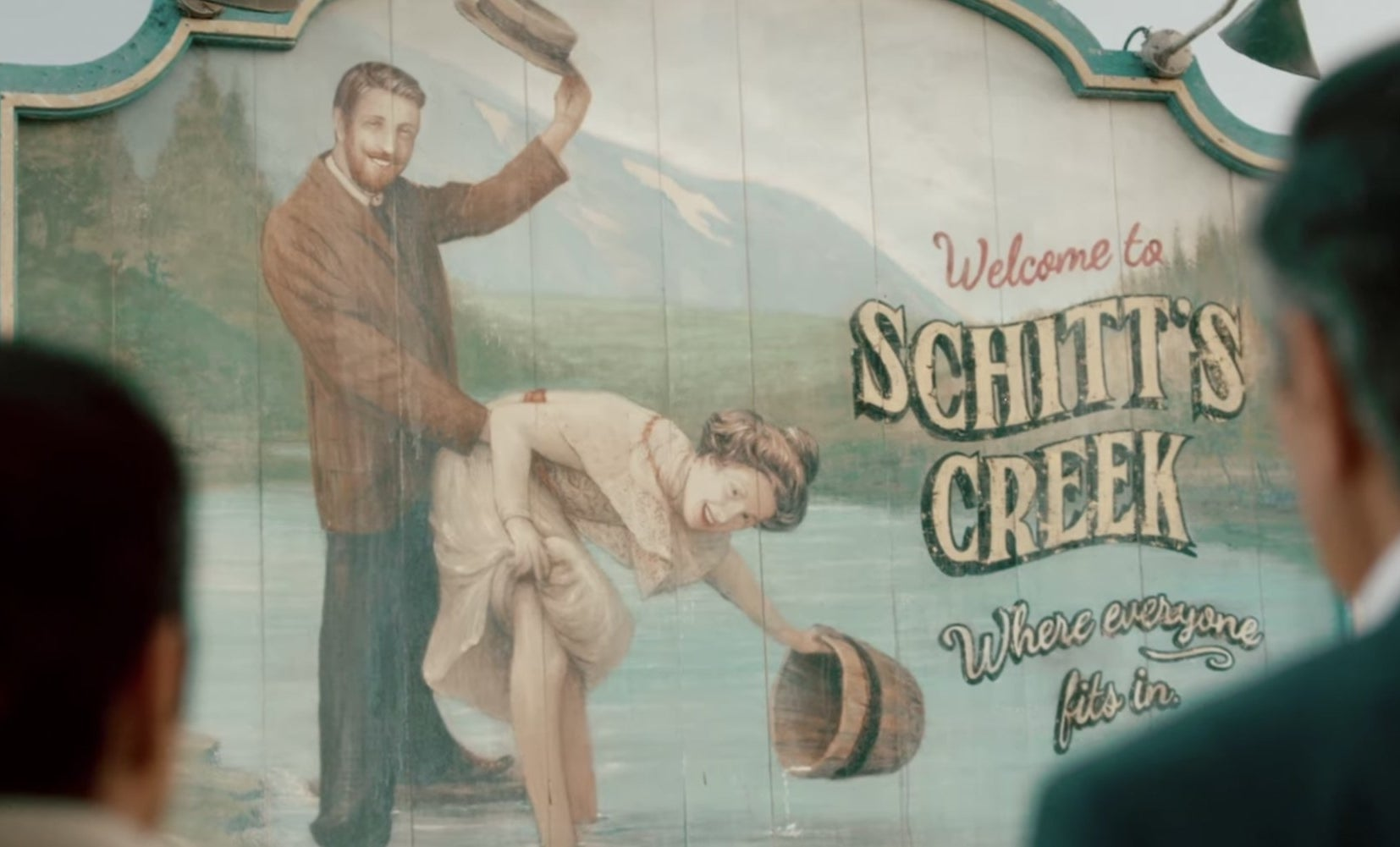 Schitt's creek town sign, man and woman suggestively in river