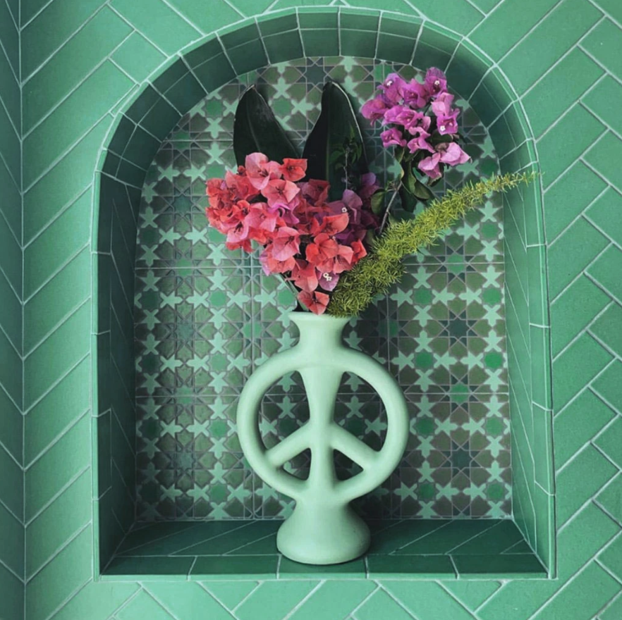 the peace sign-shaped vase in mint with flowers in it