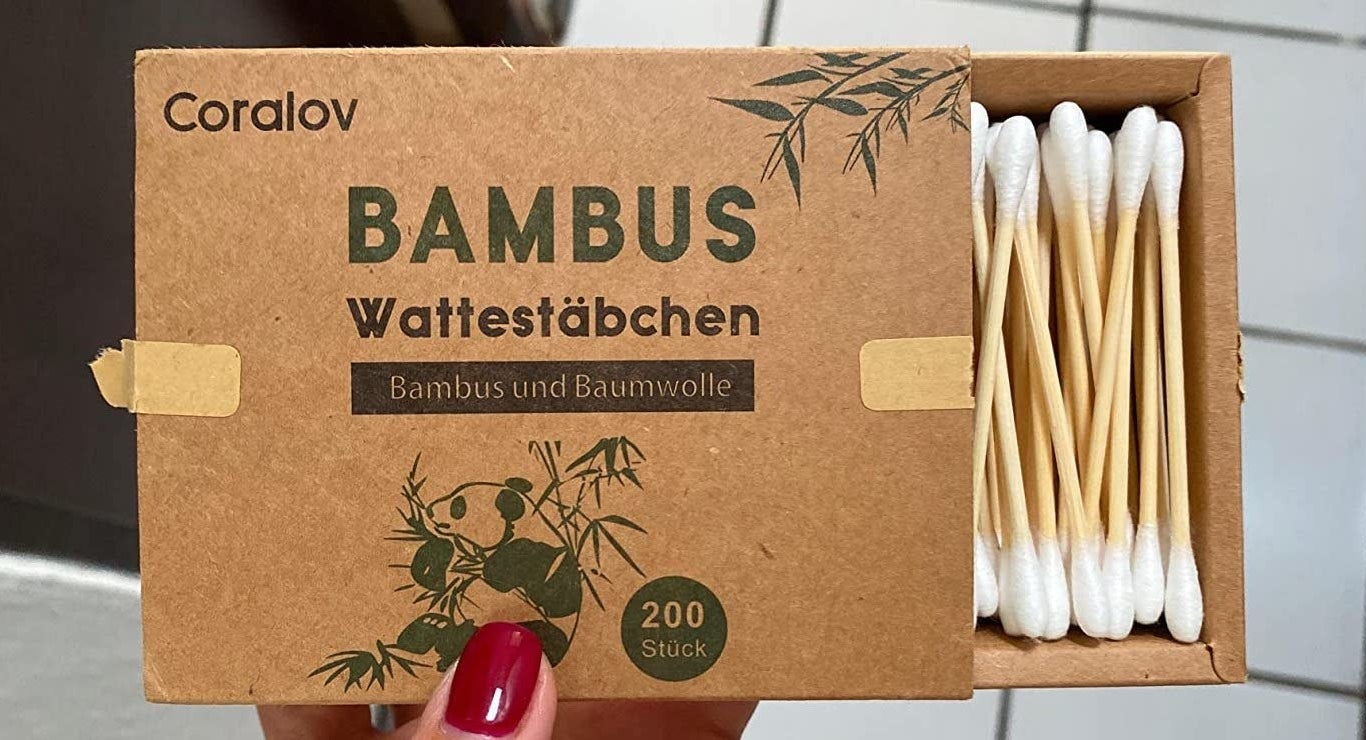 A reviewer photo of a hand holding a cardboard box partially open to show bamboo cotton swabs inside