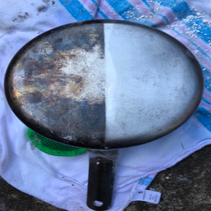 Reviewer's pan dark and rusty on the bottom on one half and shiny new on the half that was cleaned with the product