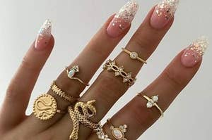 A hand wearing all the rings in the set