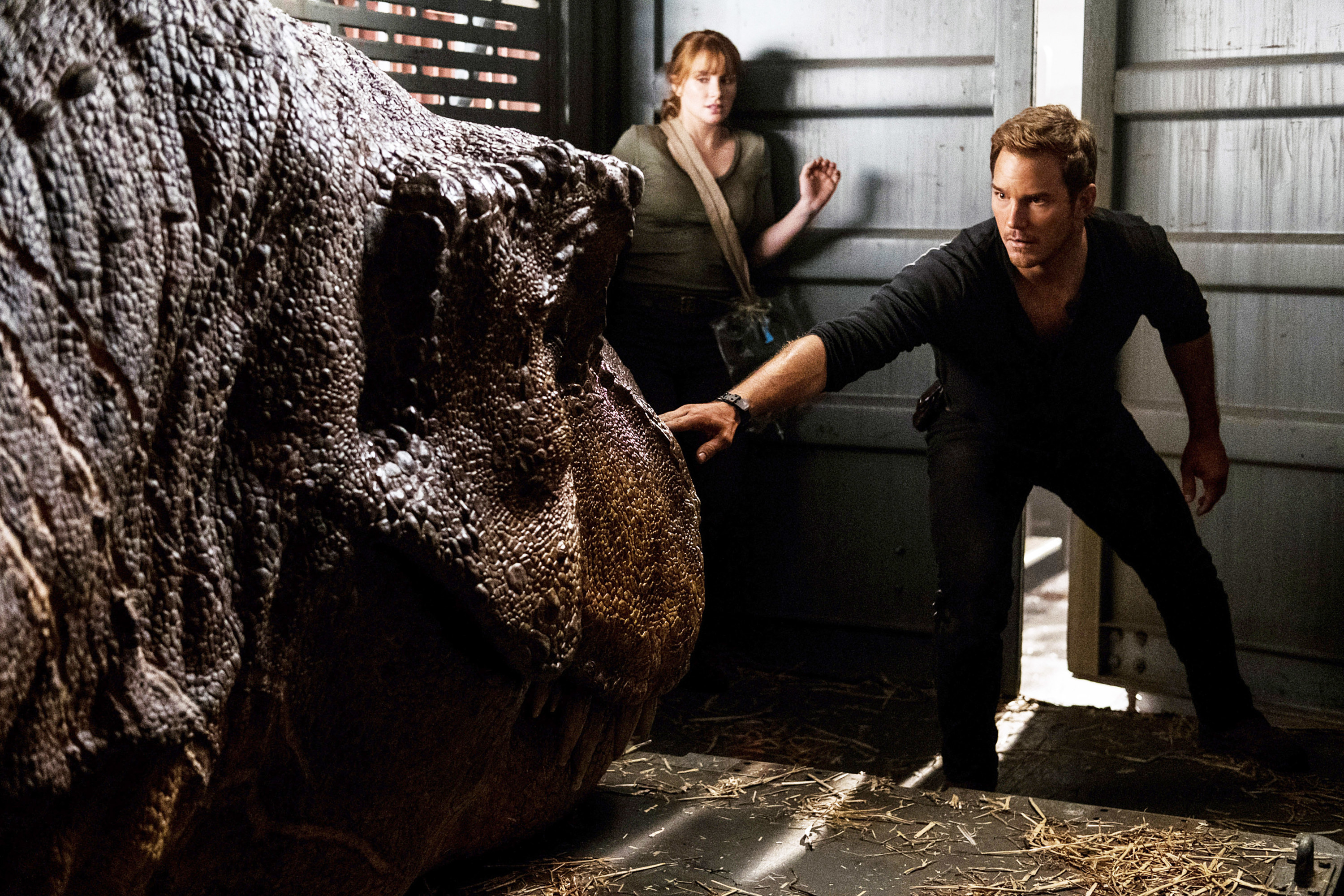 Owen Grady stands with an arm out to calm down the Indominus