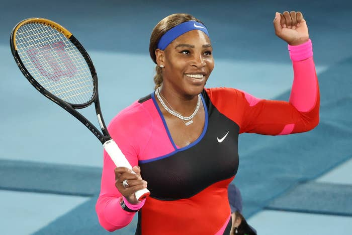 Serena smiles while holding her tennis racket on the court