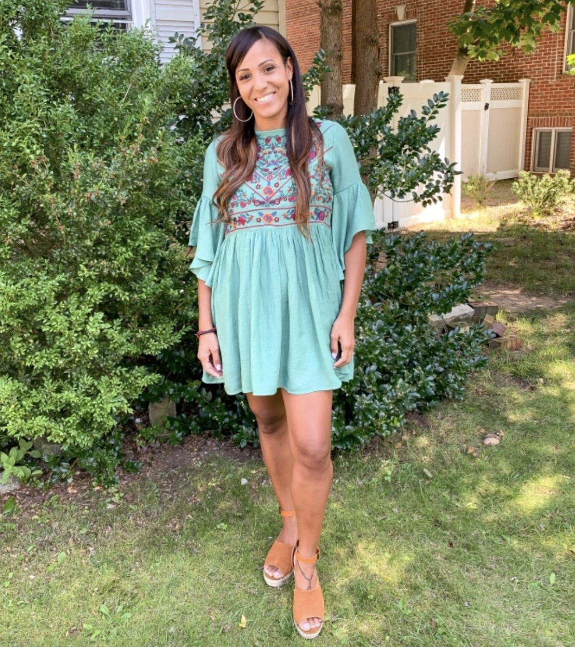 reviewer wearing the blue dress with embroidery