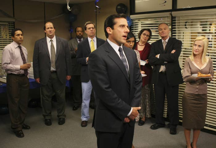 The cast of The Office standing in a meeting room