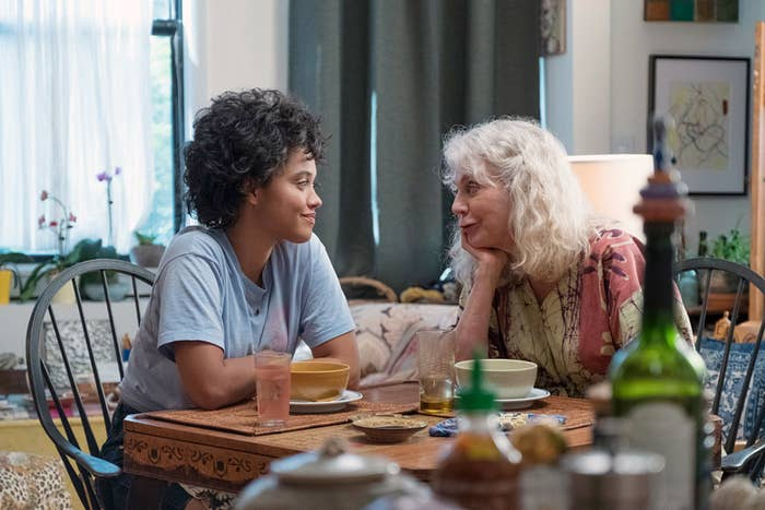 Kiersey Clemons and Blythe Danner sitting at the dining table and smiling at each other