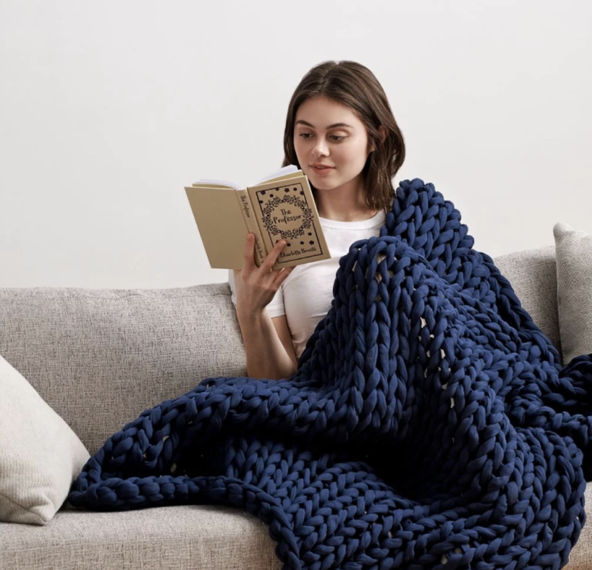 person under the knitted blanket on a couch