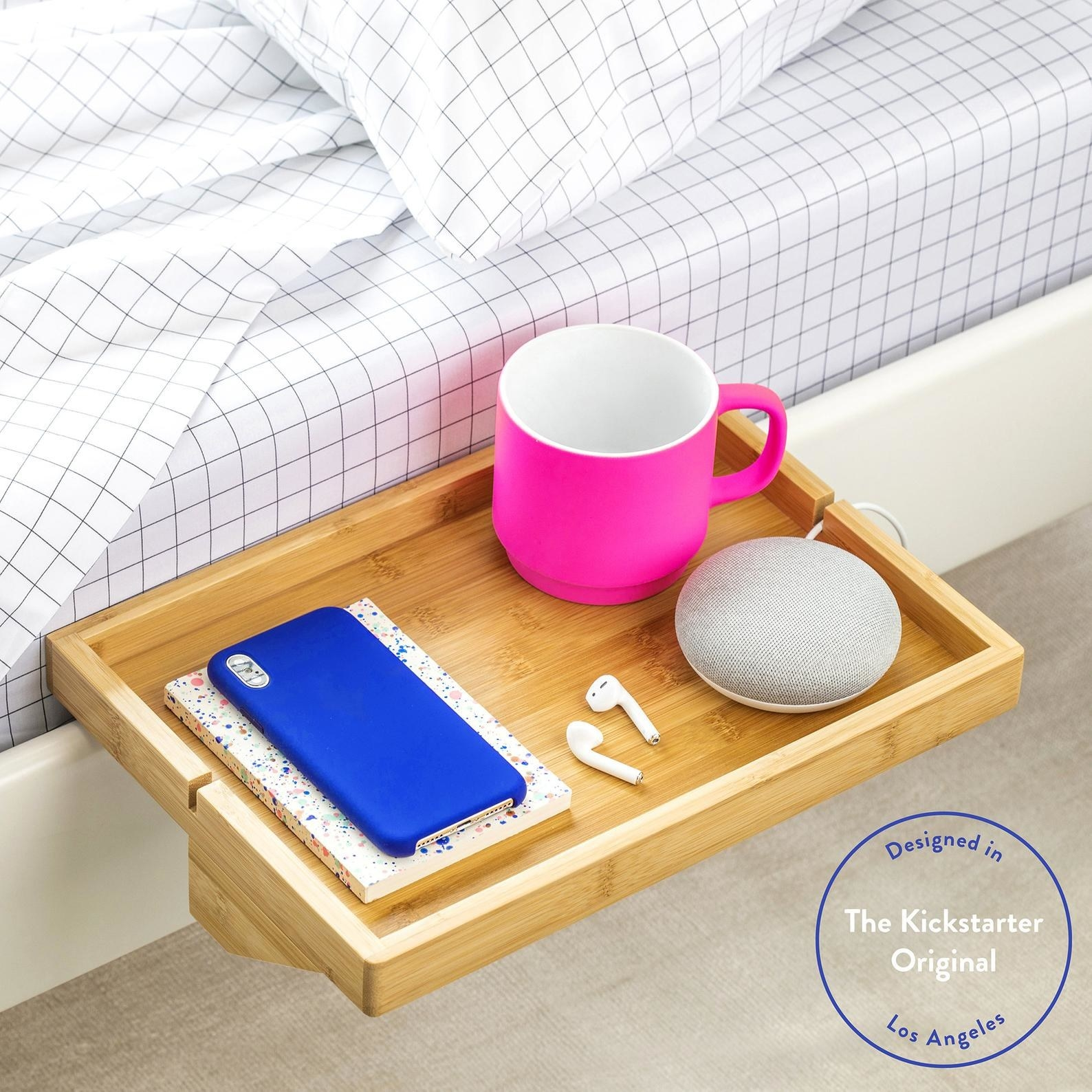 side of bed with simple shelf on the bed frame holding phone, speaker, coffee mug