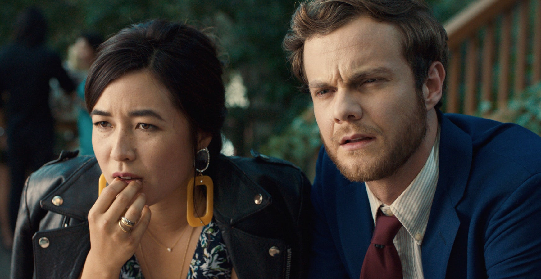 Maya Erskine and Jack Quaid looking serious while sitting down at an event