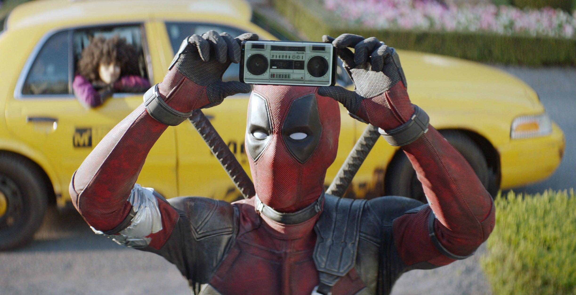 Ryan Reynolds as Deadpool holding a mini boom box