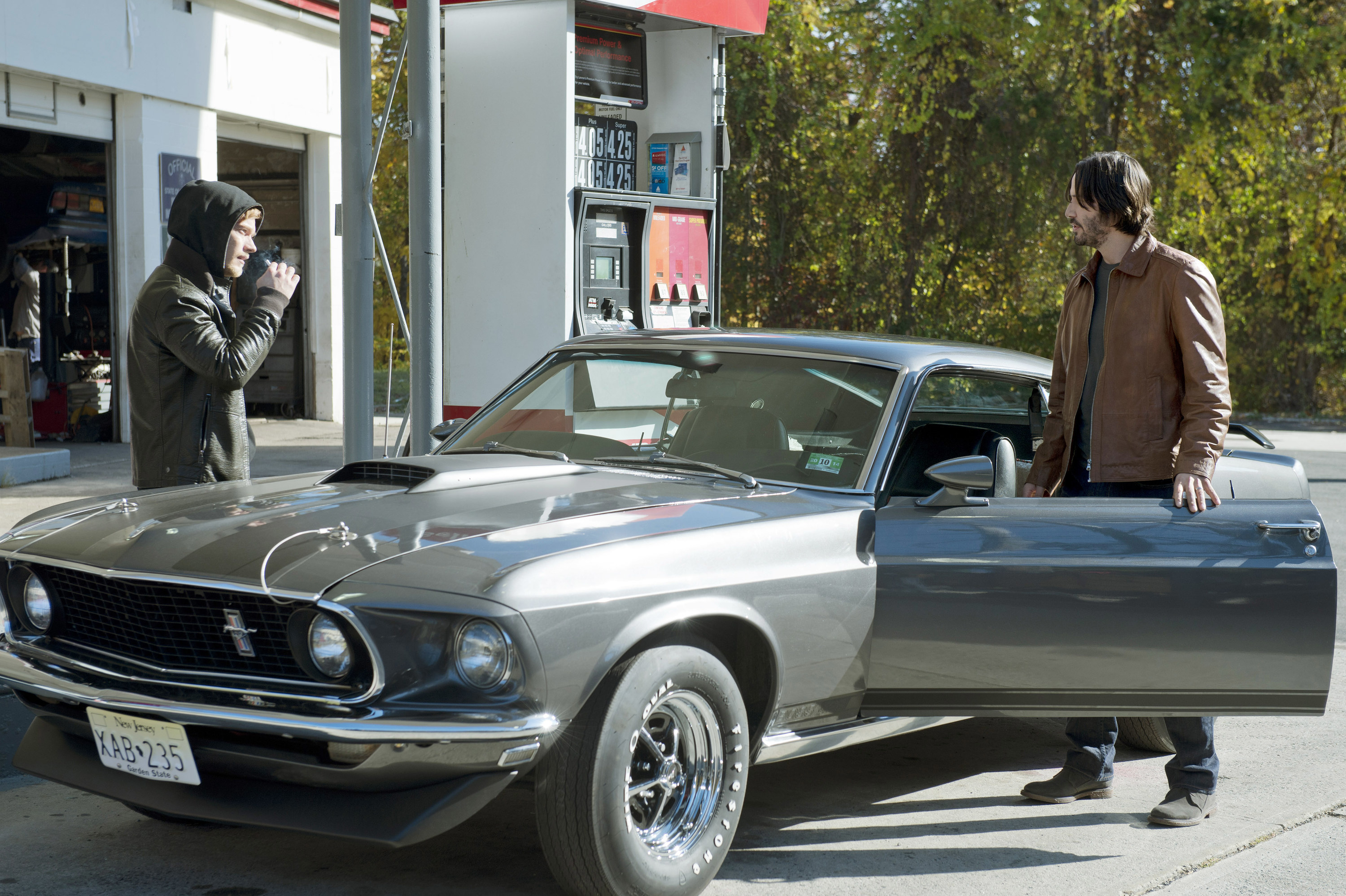 John Wick stands outside his car at the gas station as Iosef threatens him