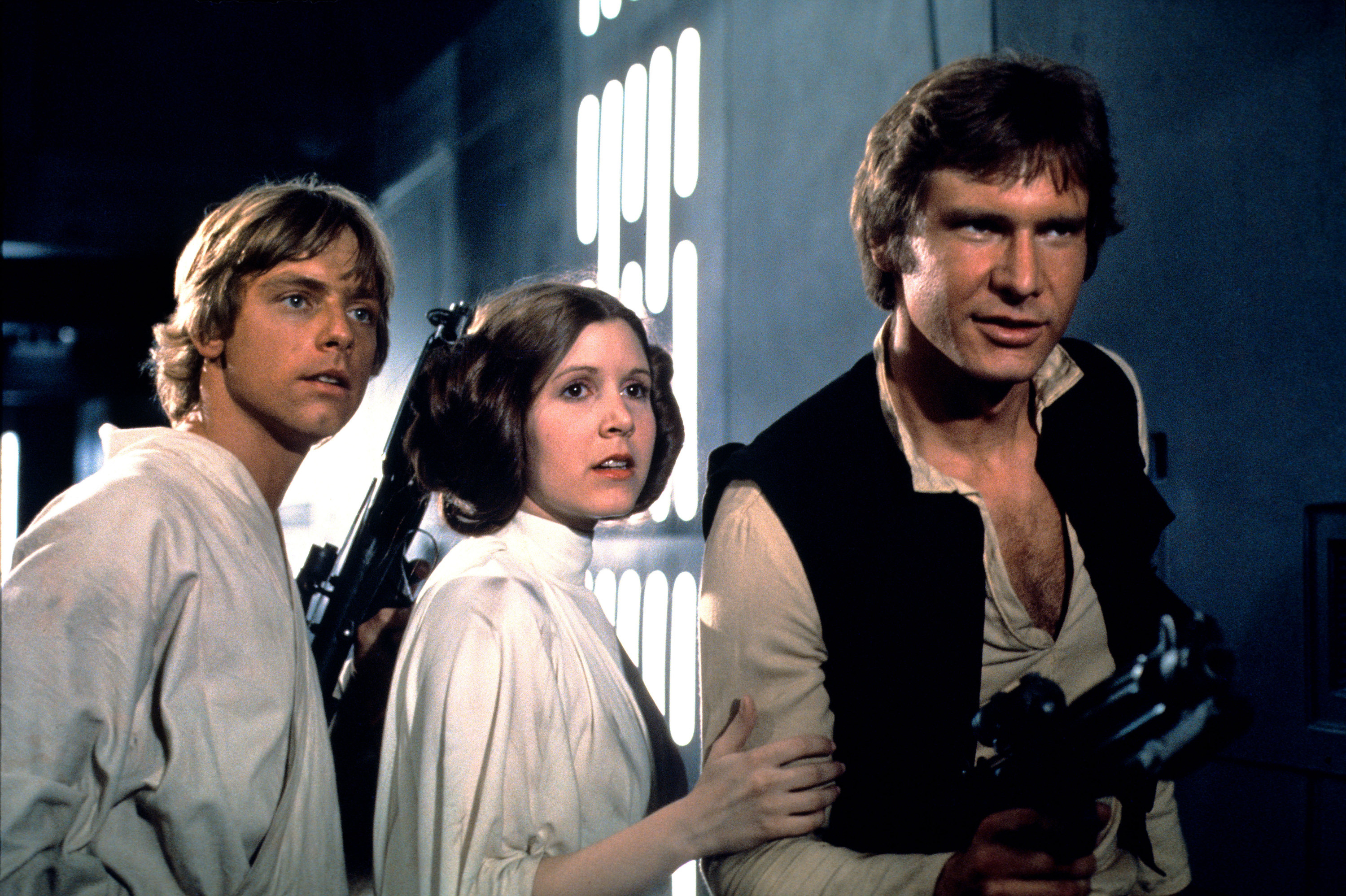 Leia stands between Han and Luke, who both hold blasters