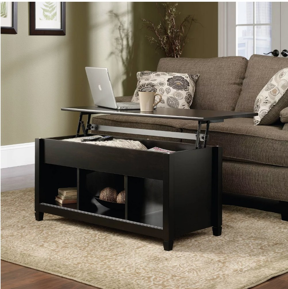 A black coffee table with a lift top for storage and 3 cubbies below filled with decor items
