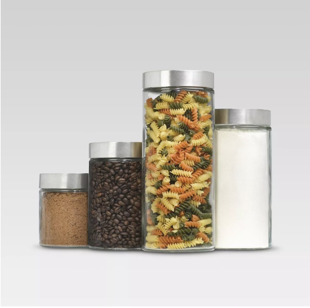 A set of 4 uniquely sized glass cylinder canisters filled with coffee beans, sugar, and pasta