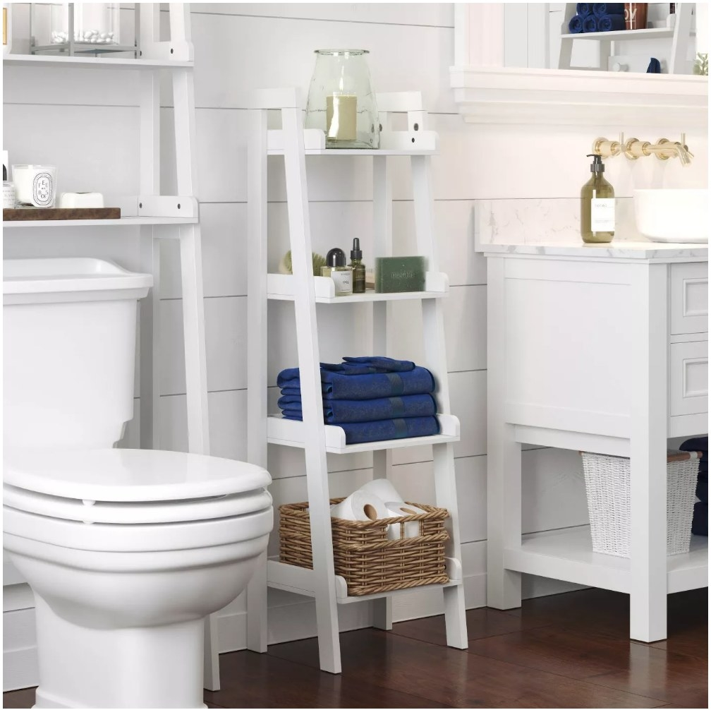 A ladder shelf with 4 shelves in a bathroom stocked with towels, extra toilet paper, decor, and toiletries