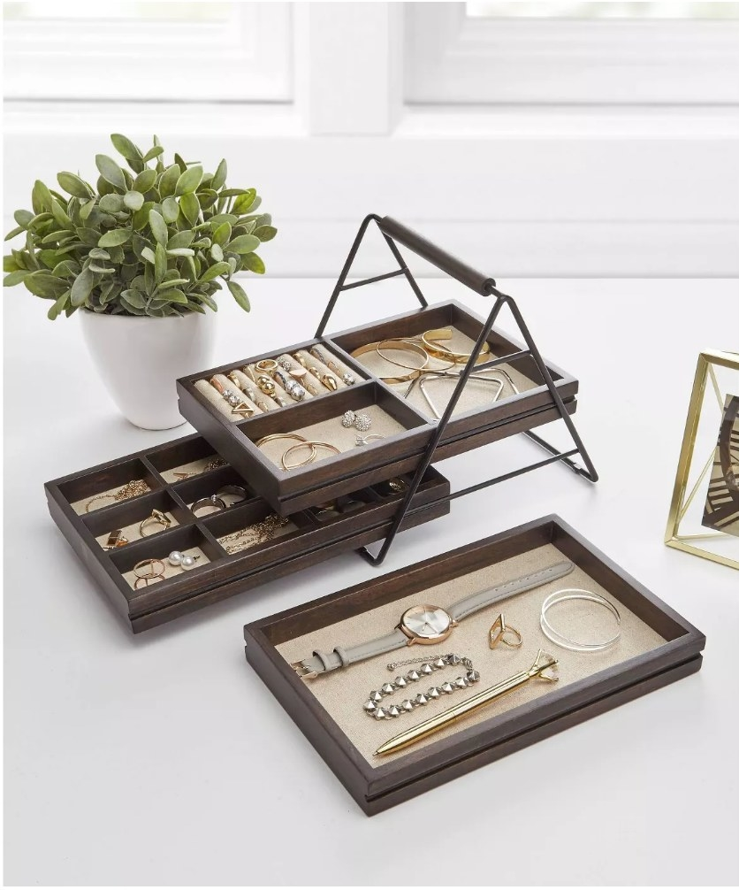 A 3-tier wooden jewelry storage box with linen interiors filled with rings, necklaces, watches, and bracelets