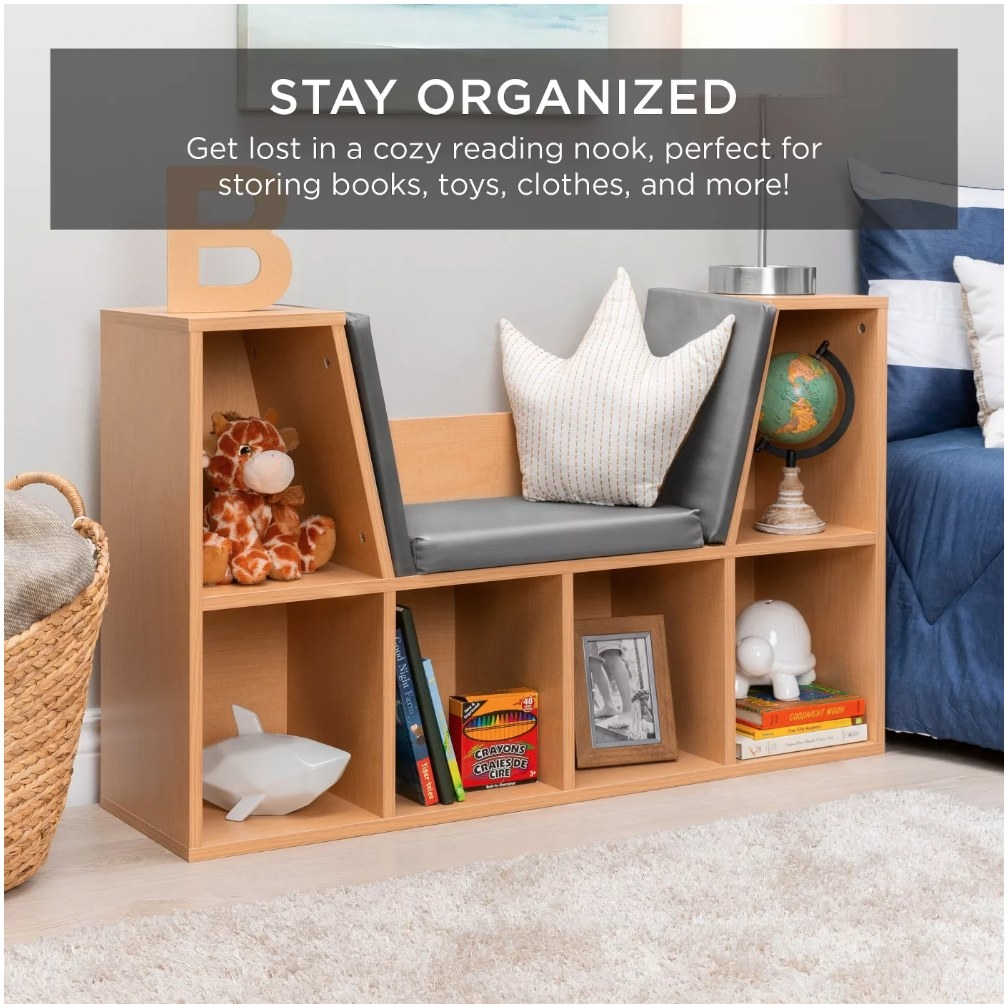 A bookcase with 6 cubbies for books and toys below a cushioned reading nook for kids