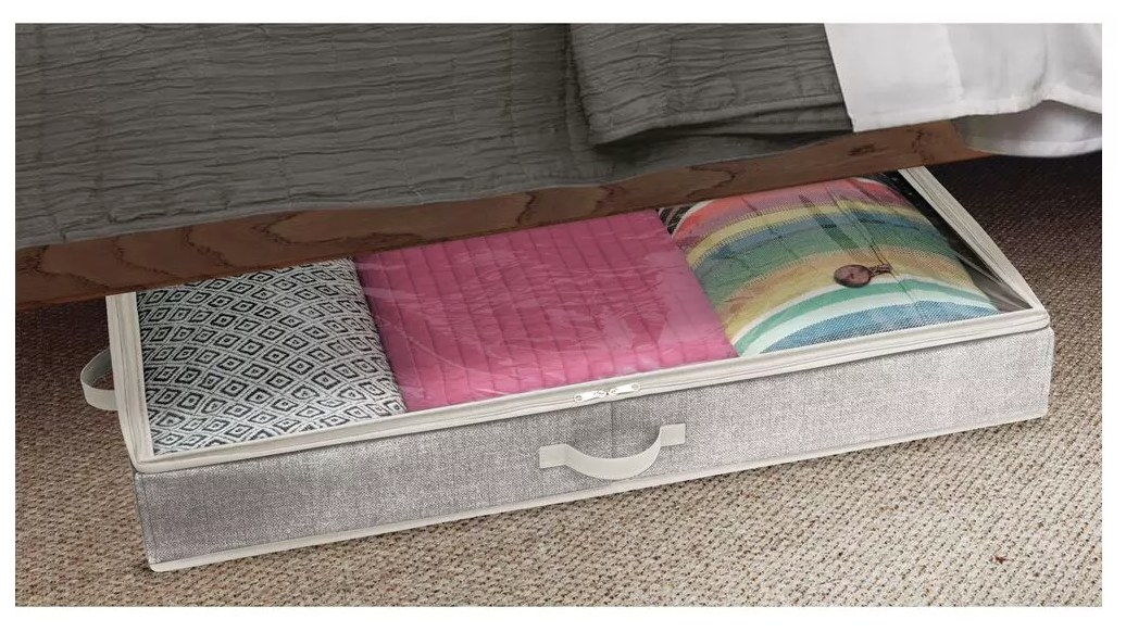 A fabric, zippered storage organizer filled with clothing and bedding under a bed
