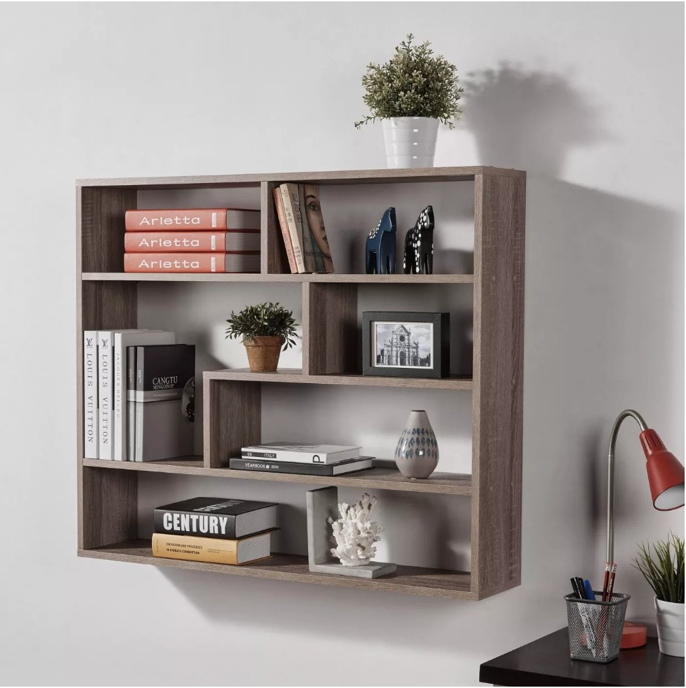 A brown, weathered oak shelf unit mounted to a wall filled with books, plants, and decor items