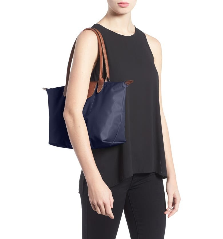 A model wears the purse in New Navy to demonstrate how it sits on the shoulder and comes down to the waist.