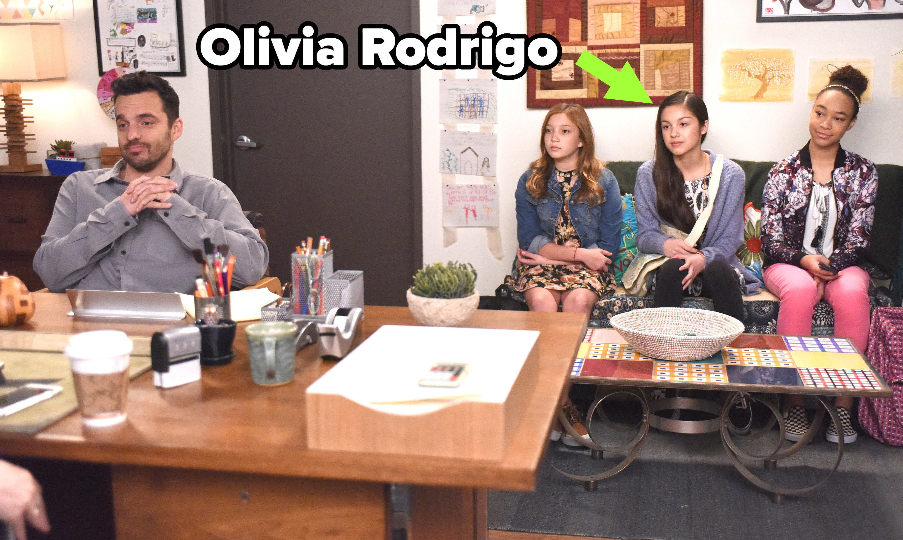arrow pointing to Olivia next to two other girls behind Nick in Jess's office on New Girl