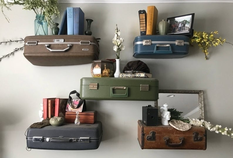 five vintage suitcases hung on the wall holding knicknacks