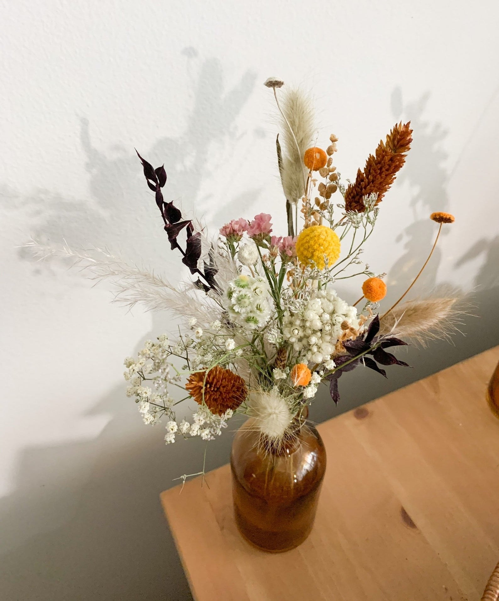the rustic dried arrangement in an amber vase