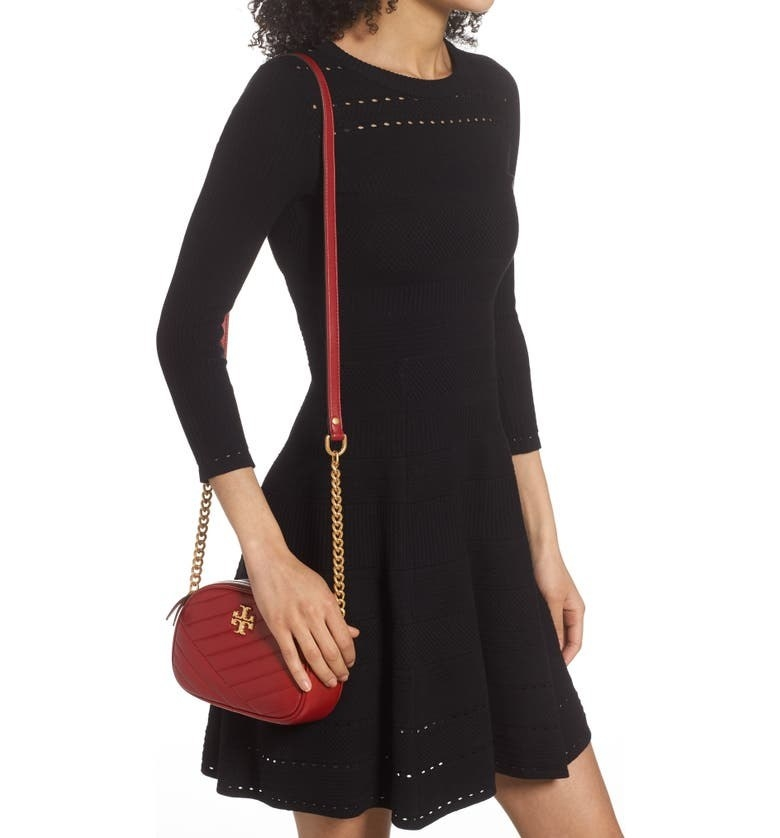 A model pairs the bag in Redstone/Rolled Brass with a black long-sleeved A-line dress